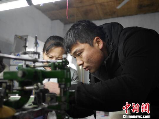 车间的技术指导正在教授刚刚进厂的女工最基本的操作苍雁摄