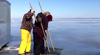 男子用电锯割开冰窟窿 然后用鱼叉捉鱼