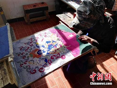米玛次仁徒弟在制作直孔刺绣唐卡。中新网记者 宋宇晟 摄
