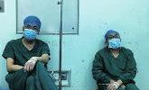2名医生趁手术间隙靠墙打点滴 已连续工作10小时