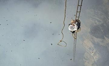 男子爬150米悬崖放烟采蜜