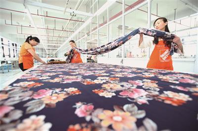无数的能工巧匠撑起盛泽发达的纺织业。图为华佳制衣车间工人在加工服装。