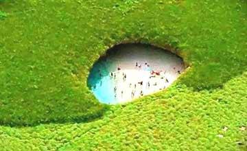 一片绿地下竟藏着超大洞穴 凑近一看竟这么多人