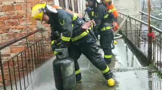 景德镇一民房起火 消防员拎着冒烟煤气罐往