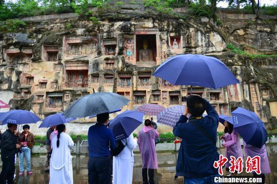 海外华文媒体冒雨参观始创于南北朝的巴中南龛石窟摩崖造像群