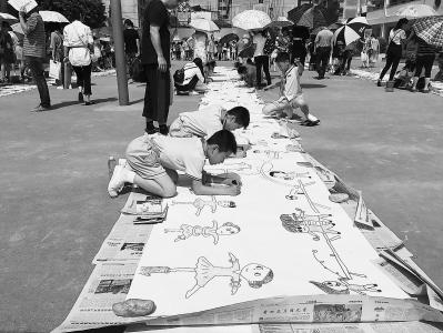 罗江小学的学生们在操场创作漫画长卷。