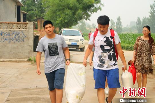 张景尧等学生代表将师生们捐赠的生活用品送往山区学生家里。 崔涛 摄