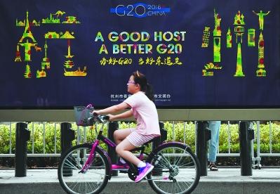 一个小朋友骑车从g20宣传画前