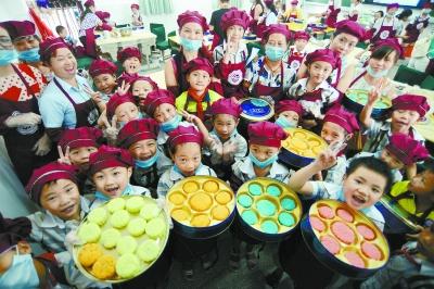 """当天,该小学开展""""做月饼,庆中秋""""主题活动,700名小学生在老师和家长的"""