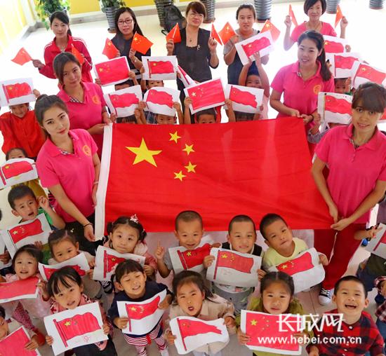 秦皇岛社区小朋友手绘国旗迎国庆 大家开心地展示绘制完成的五星红旗.