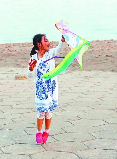 汉口江滩,一名女孩跳起来放风筝.记者杨少昆 摄-黄金周 欢乐季图片
