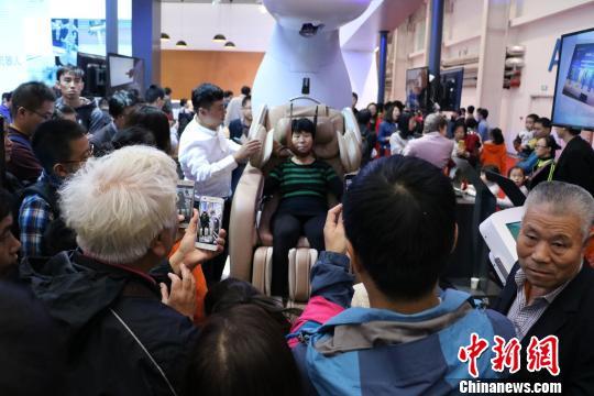 2016世界机器人大会25日在北京亦庄闭幕。一批医疗、康复类机器人尤为引人注目。图为观众体验康复机器人。 曾鼐 摄