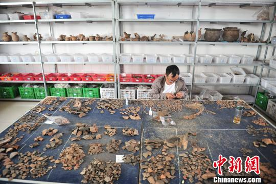 图为工作人员对出土的陶器碎片进行修复刘冉阳摄