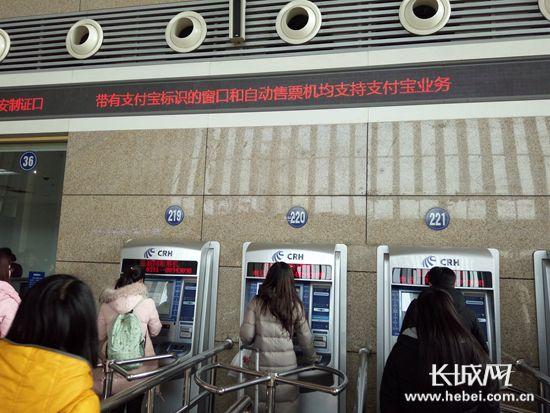石家庄站西广场售票大厅,搭客们正在通过自助终端购置车票。苏凯 摄