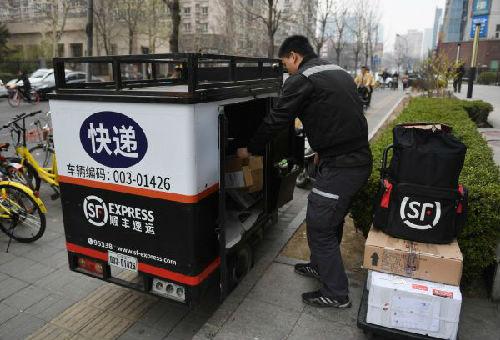 一名快递员17日在北京街头整理包裹。(法新社)