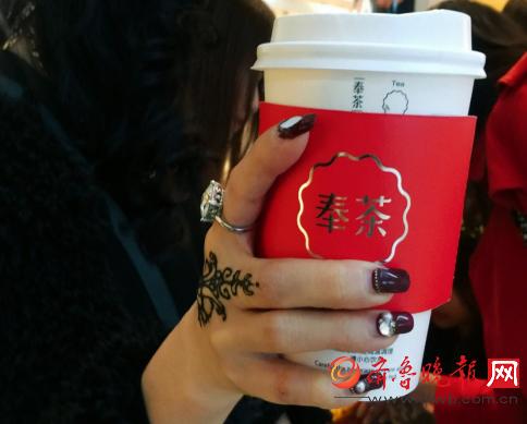 穿着时尚的海娜手绘师skye,正专注地在女孩的手背上画着精美的图案.