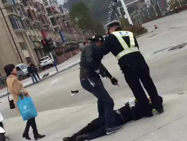现场图片显示,一名身着警察执法的男子躺倒在地,一男子双腿跨站在其身上,左手指指点点疑似谩骂,旁边另一名身着警服人员进行劝阻。