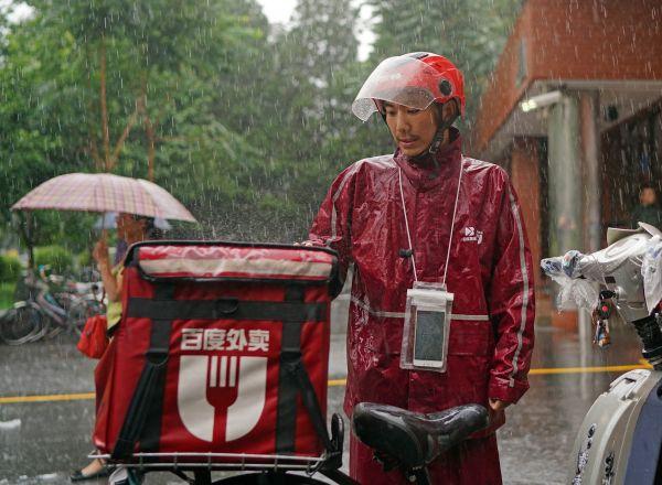 外卖送货员在暴雨中坚持工作。新华社记者陈诚摄