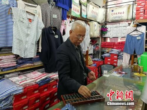 61岁的售货员张志国至今仍在使用算盘中新网记者张尼摄
