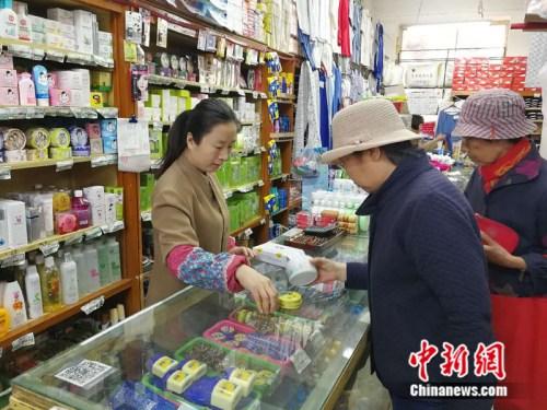 顾客在永安路百货商场化妆品柜台挑选商品中新网记者张尼摄