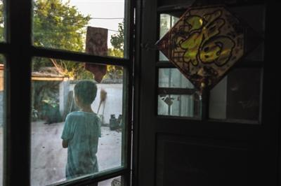 8月8日,山东郓城县西张楼村,张超12岁的弟弟独自一人站在屋外望着大门口。他的父亲前往天津询问案情进展未回,母亲因极度悲伤卧床不起,屋里屋外全靠弟弟张罗。新京报记者彭子洋摄