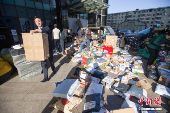 上午,多家快递企业的工作人员在商业中心扎堆分发快递,以此提高效率。 张云摄