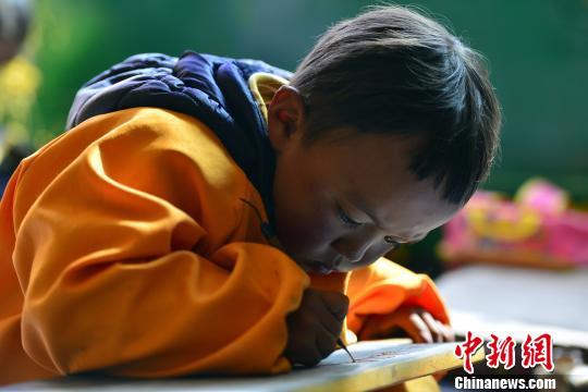 傳統的藏文書法練習方式要求練習者盤腿而坐,一手按穩墻星,一手書寫。 周文元攝