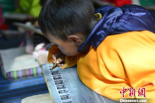图为正在以传统方式练习藏文书法的藏族小学生。 周文元摄