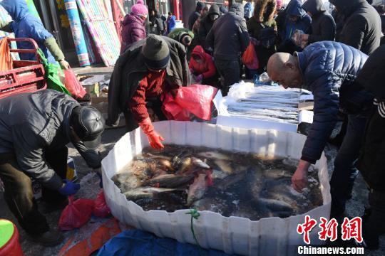 摊主搅动着水里的冰碴,捞出一条大鱼,兴奋地称重。 张瑶摄