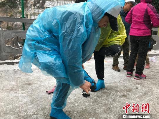 游客穿着雨衣、钉鞋上山。 汪钰摄