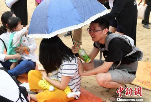资料图:2017年5月,近200福州辣妈进行街头哺乳快闪活动,图为活动中一位丈夫帮妻子撑伞。 吕明摄