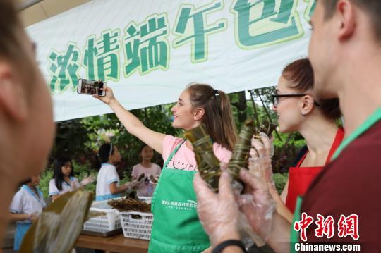 外国女性尤利娅用手机拍摄包粽子的场景李星凯摄