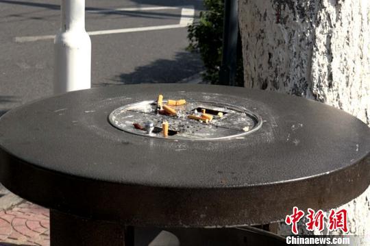 图为街边垃圾桶上堆积的烟头。 梅镱泷摄