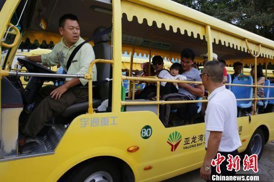 热带天堂森林旅游区,魏锦辉(右侧白衣者)在指挥车辆进出。 王晓斌摄
