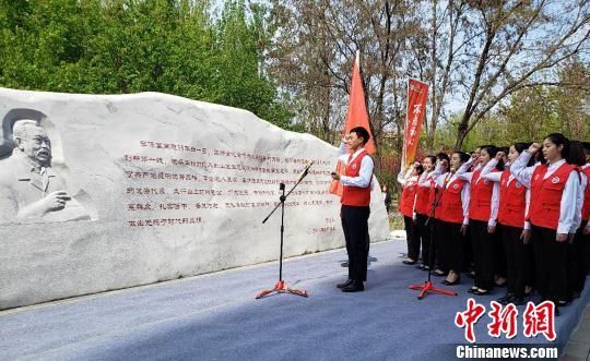 """""""李保国扶贫志愿服务队""""志愿者代表在李保国纪念石前宣誓。 徐巧明摄"""