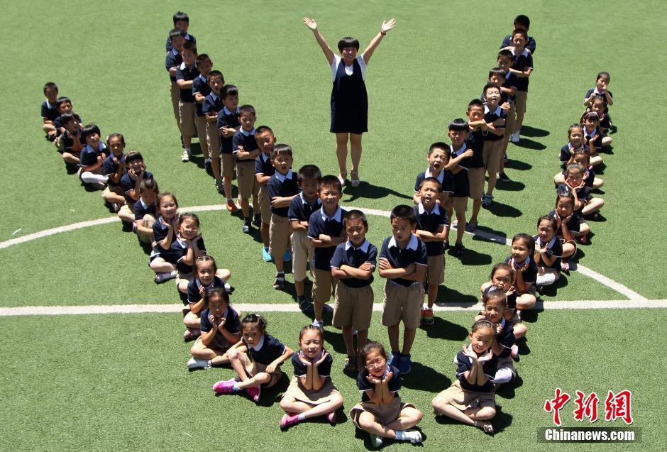 """石家庄一年级小学生""""结业照"""" 6月24日,在河北石家庄市保利启新小学的操场上,由学生组成的""""one""""字图形、""""花朵""""图形等各种创意无限的图案,吸引了众多师生的目光。据介绍,这场媲美大学经典毕业照的创意""""结业照"""",是由该校一年级升二年级的小学生及他们的老师和家长合力完成。一组组图案中,孩子们的童年将就此定格。"""