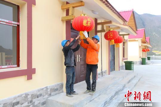 搬迁工作人员为房屋挂上红灯笼 钟欣 摄
