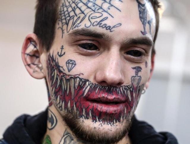 这名男子脸上充满了恐怖的纹身,蜘蛛网,充满獠牙的怪物牙齿惊人不寒而图片