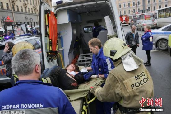 """图为""""先纳亚广场""""地铁站爆炸事件的伤员被抬上救护车。"""