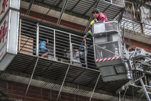 台北市中华路二段的老旧公寓发生火警,住户在阳台等待消防人员来救援。台湾《联合报》记者杨万云/摄影