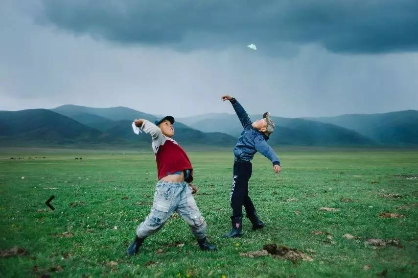 暴风雨来临前,两名男孩放飞手中的纸飞机.图片