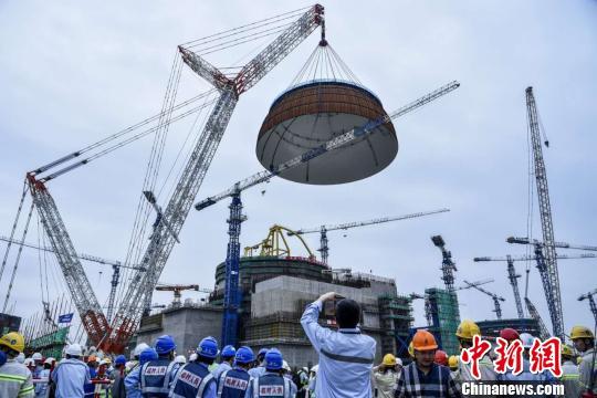 """5月25日下午5时58分,中国自主三代核电""""华龙一号""""全球首堆示范工程�D�D中核集团福清核电5号机组穹顶吊装成功,这标志着5号机组已全面进入设备安装阶段。 钟鹰 摄"""