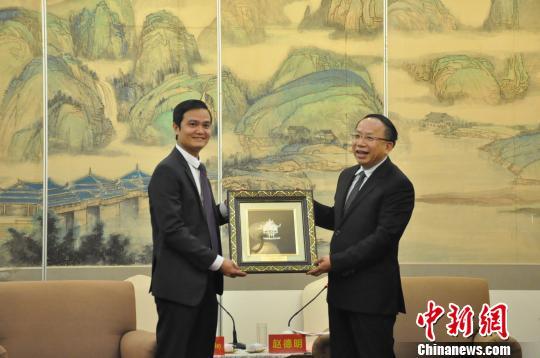 图为裴光辉(左)将一幅越南特色工艺品赠送给中方。 钟建珊 摄