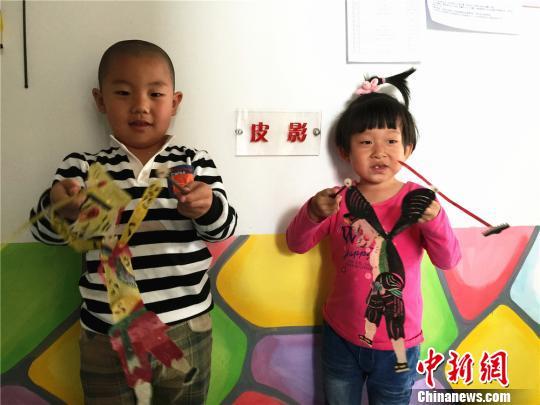 老师们还大展身手制作了皮影西游记。图为小朋友展示孙悟空和猪八戒的皮影造型。 史静静 摄