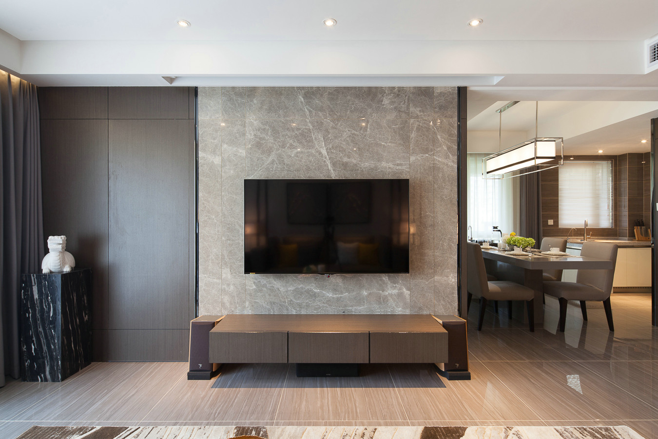 ▼电视背景墙采用灰色大理石并用黑色不锈钢收边,低调,沉稳又内敛,靠