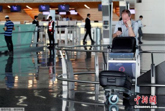 此前,阿联酋航空、埃及航空等相继暂停往返卡塔尔首都多哈的航班,沙特等国甚至禁止卡塔尔航空班机越过领空,令中东航空枢纽多哈的哈马德国际机场陷入混乱。图为一名游客在哈马德国际机场看手机。