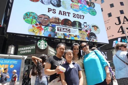 中国侨网赵可心(左二)与母亲(左一)、学校副校长(右一)等在时报广场艺术作品展屏幕前。(来源:美国《世界日报》/金春香 摄)