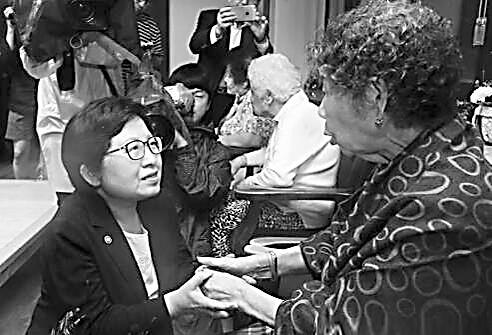 """图说: 郑铉栢与""""慰安妇""""受害者交谈。"""