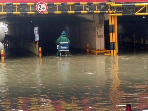 送餐小哥涉水而过 14日下午,济南白鹤装饰城铁路桥洞积了半米多深的水