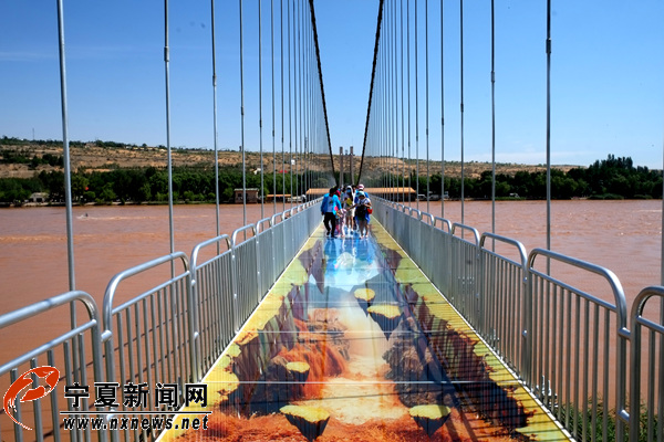 黄河3D玻璃桥。   宁夏新闻网讯(记者 姜盼)7月31日上午,黄河3D玻璃桥运营启动仪式在宁夏中卫沙坡头景区举行,从此宁夏人无需远行就可以在家门口体验到玻璃桥的惊险与刺激。黄河3D玻璃桥的建成,为来到国内老牌5A级旅游景区港中旅(宁夏)沙坡头游玩的游客,带来除了乘坐羊皮筏子、黄河飞索外的另一种感受黄河风光的新奇方式。   据了解,沙坡头悬索桥于2004年建成,建成之初桥面由木板铺设而成。2017年,沙坡头旅游景区实施提质扩容工程,累计投资2000万元,将悬索桥在原本基础上改造成了黄河3D玻璃桥。